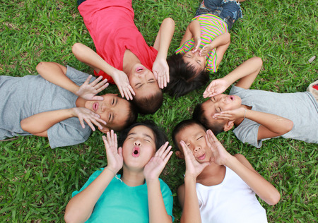 school activities: Six children cover their face with green glass background.