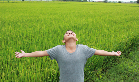 asian children: Young asian boy with green rice field background.