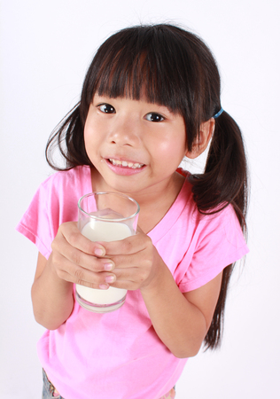 innocent girl: Young girl drinking milk. Stock Photo