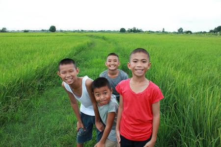 pobre: Cuatro niños en el campo de arroz.