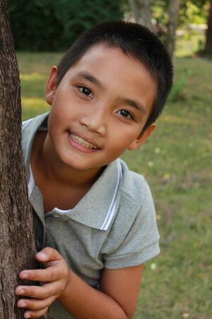 3 persons only: Portrait of young happy boy behind tree at park. Stock Photo