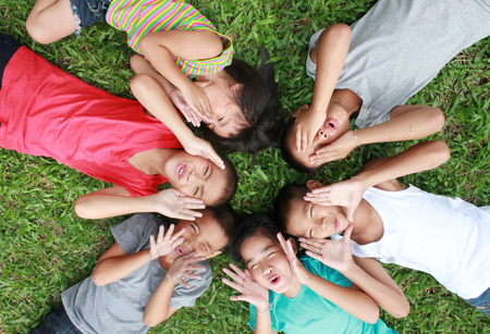 niños sonriendo: Seis niños jugando en el parque.