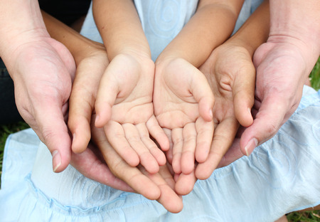 trust: Adult hands holding kid hands Stock Photo