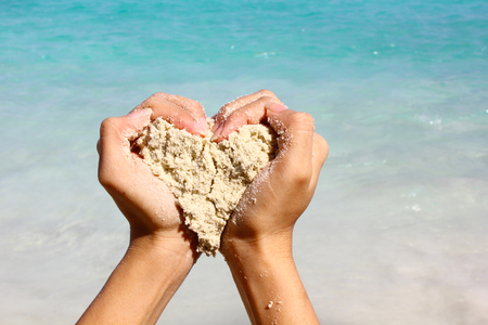 heart hands: Closeup hands holding white sand heart shape with beautiful beach