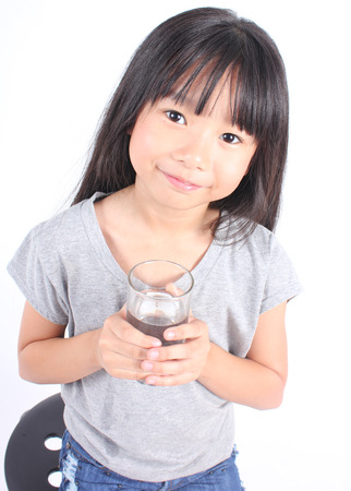 copa de agua: Young little girl drinking water.