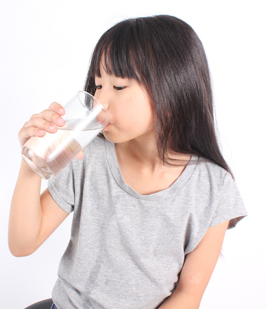 object glass: Young little girl drinking water.