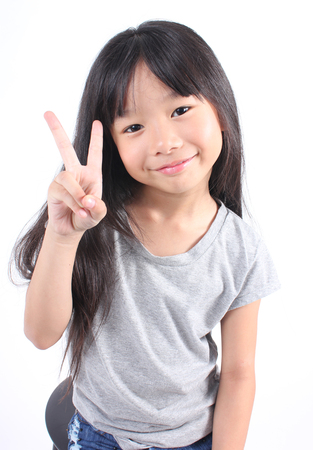 Portrait of young cute girl posting with two fingers. Stock Photo