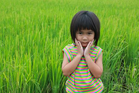 pobre: Niña de pie en el campo de arroz.
