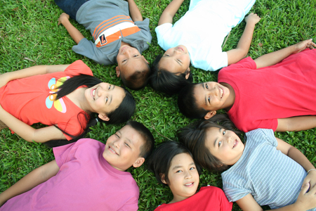 Seven children sleeping in the park.