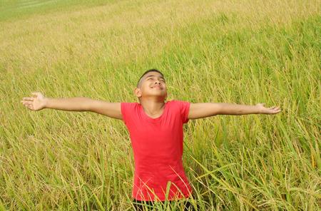 pobre: niño feliz con el fondo del campo de arroz.