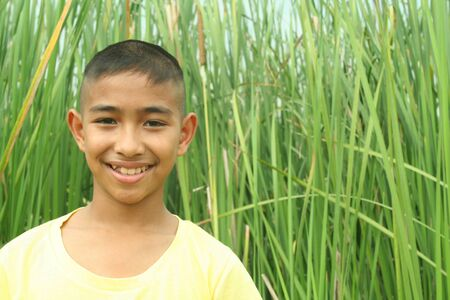 asian boy: Young asian boy with green rice field background
