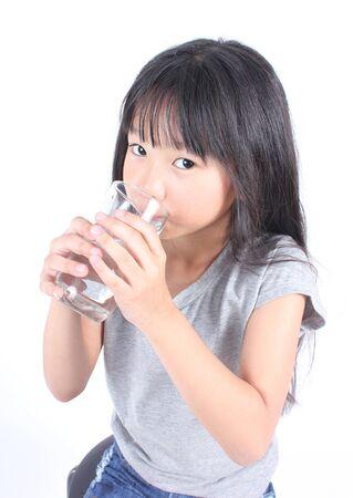 agua purificada: Niña joven con un vaso de agua. Foto de archivo