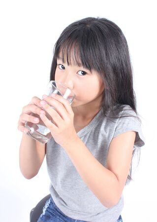 hold on: Young little girl holding a glass of water. Stock Photo