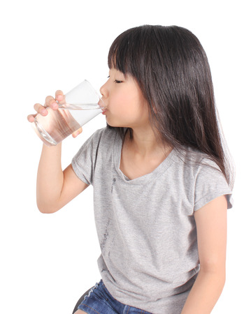 girl drinking water: Young little girl drinking water.