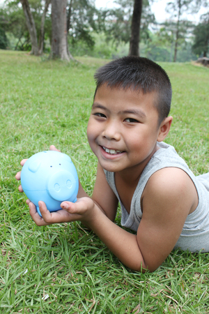 boy beautiful: Young boy holding piggy bank with green grass background