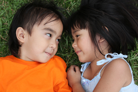 asia children: Two lovely kid looking at each other with green grass background. Stock Photo