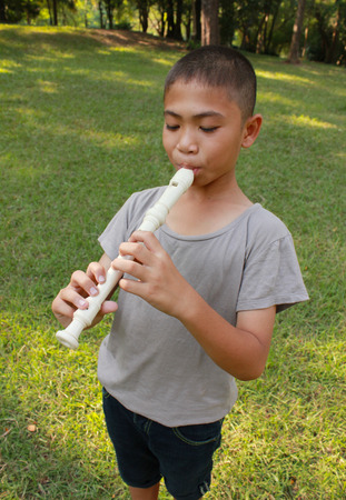 boy beautiful: Young boy playing flute in park