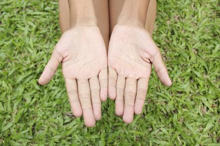 gente pobre: Dos manos con el fondo de la hierba verde.