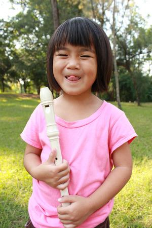 Junges Mädchen Flöte spielen im Park Standard-Bild - 51873740