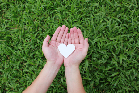 hand care: Two hands holding white heart with green grass background.