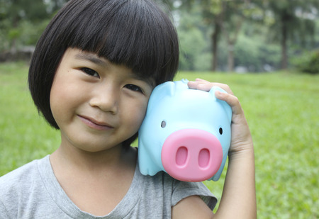 money and saving: Young girl holding piggy bank Stock Photo