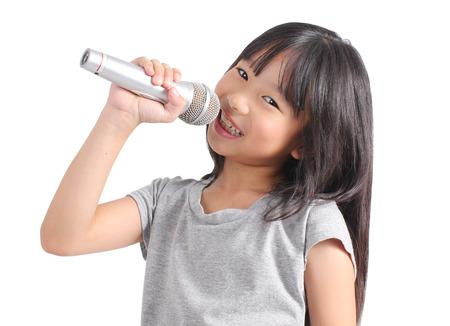 Niña bonita con el micrófono en la mano