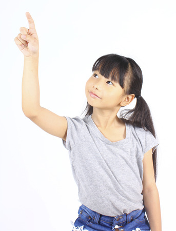 asian preteen: Little girl pointing up with her finger