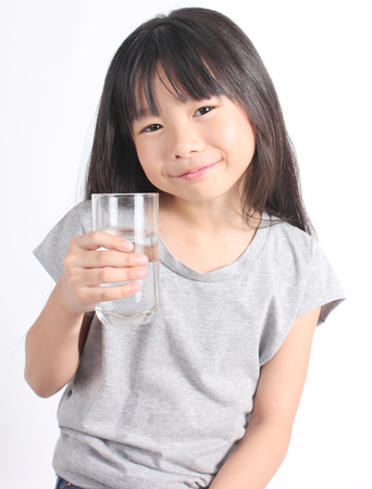 chinese drinks: Young little girl holding a glass of water. Stock Photo