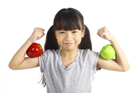 A little girl flexes her muscle while showing off the apple that made her strong and healthy
