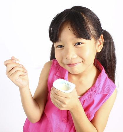 niños comiendo: Muchacha que come el yogur aislado en blanco