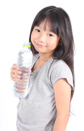 kids hand: Happy girl holding a bottle of water.