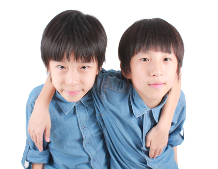 old asian: Portrait of two hugging boys, asian twins isolated on white background. Stock Photo