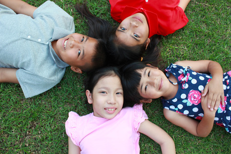 study group: Four kids having fun in the park on green grass background.