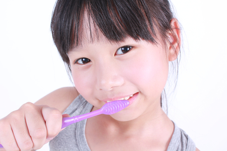 child smile: Cute girl brushing her teeth on white background.