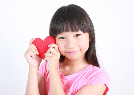 Portrait of young cute girl with red heart on white background.