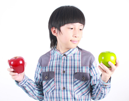 child smile: Young boy holding red and green apple on white background.