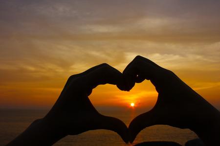 shape silhouette: Love shape hand silhouette, sun set on the beach background.