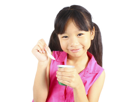 eating yogurt: Girl eating yogurt isolated on white Stock Photo