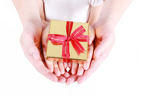 greeting season: Hands holding beautiful gift box, adult and child giving gift, Christmas holidays and greeting season concept Stock Photo