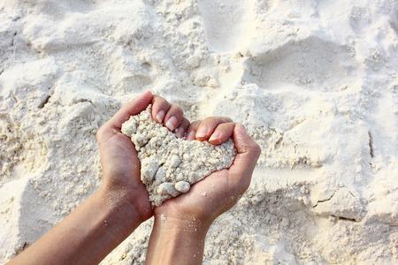heart hands: Closeup hands holding white sand heart shape, love concept.