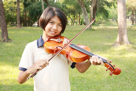 music education: Happy girl playing her violin in the park.