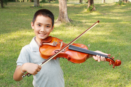 asian boy: Happy boy playing his violin in the park. Stock Photo