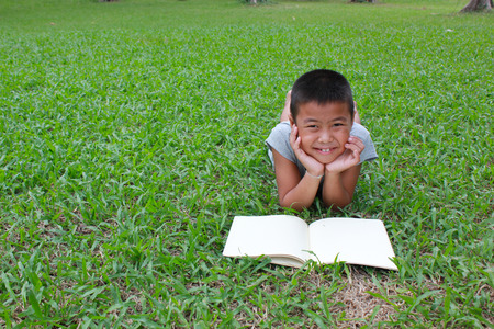 latin child: Young boy reading in the park, spring time.