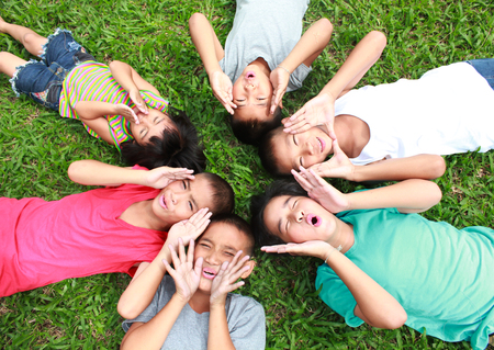 Six children playing in the park, spring time.