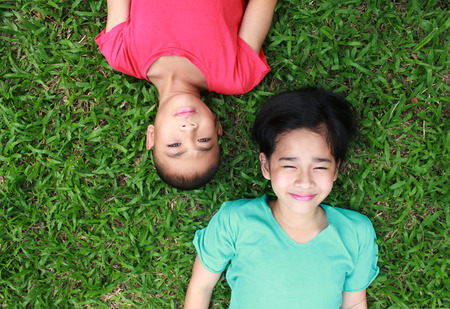 pobre: Two lovely kids with green grass background. Foto de archivo