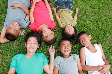 niños sonriendo: Seis niños jugando en el parque, tiempo de primavera.