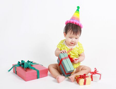 birthday presents: Cute baby laughing wearing party hat, over white background.