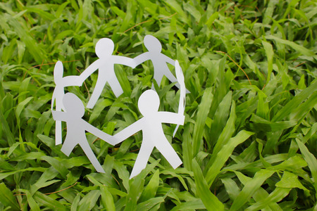 friendship day: Paper people in a circle with green grass background. world peace concept.