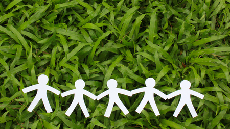 green world: Paper people in a line with green grass background. world peace concept.