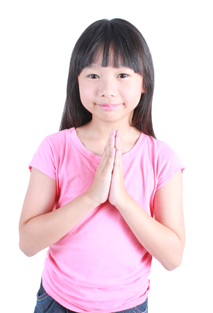Young asian girl put her hands together and pray over white background. Standard-Bild